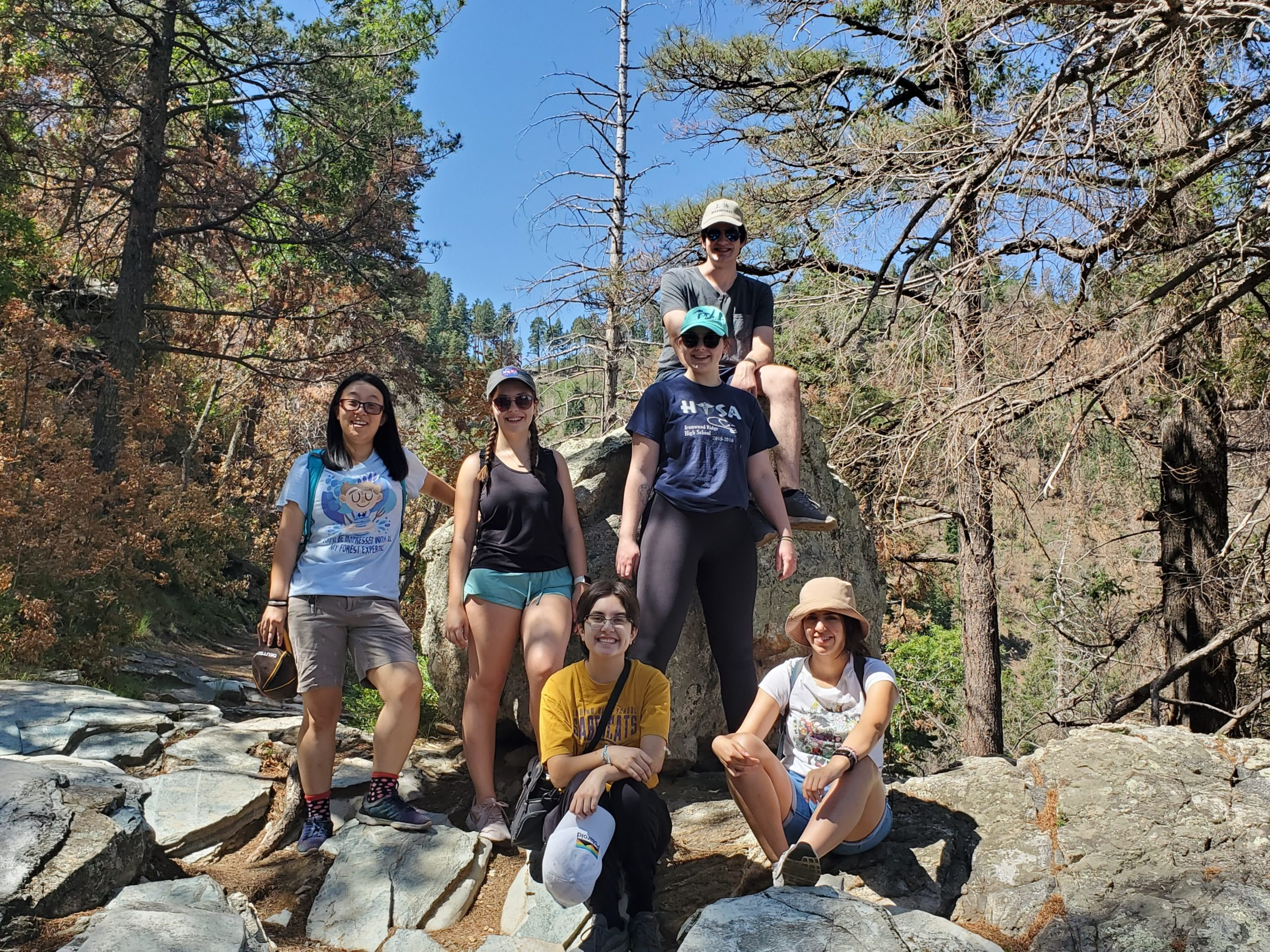 6 young adults in hiking attire standing and sitting around a large boulder.